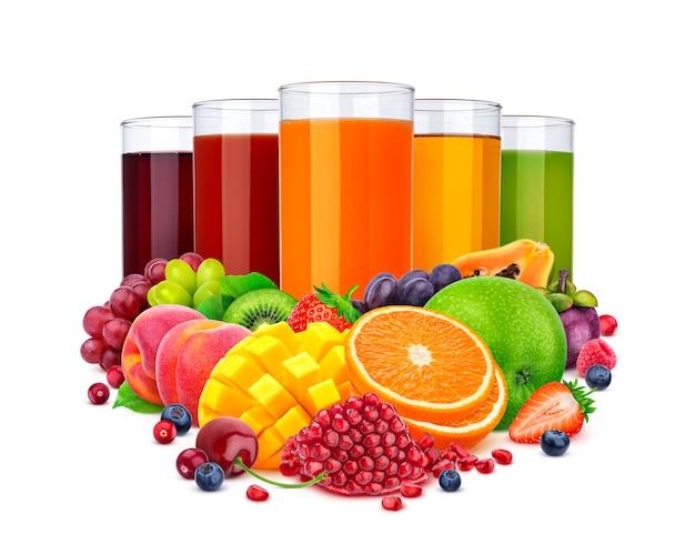 Vasos de diferentes jugos y pila de frutas y bayas aisladas sobre fondo blanco