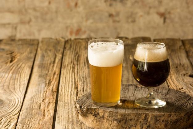 Vasos de diferentes tipos de cerveza oscura y clara en la mesa de madera