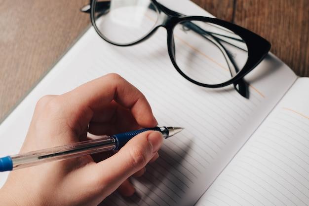 Vasos de escritura de bloc de notas en la mesa pluma en mano