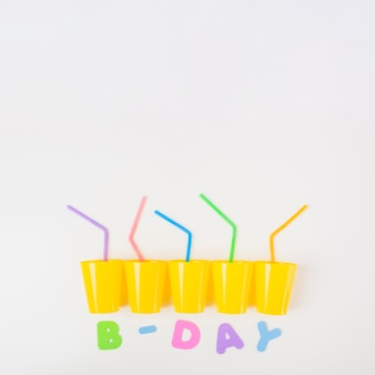Vasos de fiesta de cumpleaños con pajitas de colores sobre fondo blanco