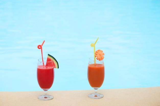 Vasos de jugo fresco sentado en el borde de la piscina