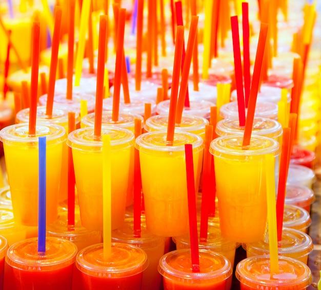 Vasos de jugo de frutas frescas de colores naturales con paja