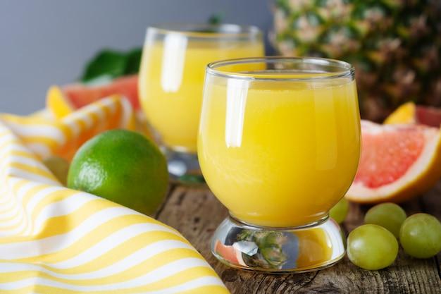 Vasos de jugo de frutas con frutas en el fondo