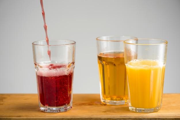 Vasos con jugo de manzana, naranja y cereza