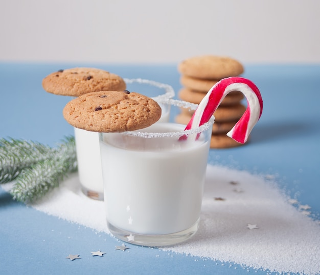 Vasos de leche, galletas, bastón de caramelo, rama de árbol de navidad en azul