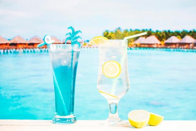 Vasos de limón fresco azul beben con paja y limón en rodajas