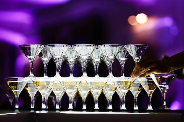 Vasos de martini hacen la pirámide en la mesa de cristal