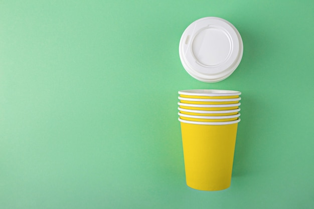 Vasos de papel amarillo desechables con tapas de plástico para llevar café o té sobre fondo verde con espacio de copia