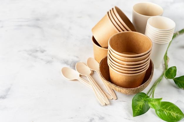 Vasos de papel y bambú, bolsa y cubiertos de madera.