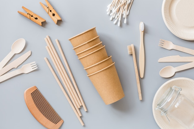 Vasos de papel ecológico natural, pajitas, cubiertos de madera planos sobre gris