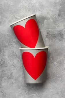 Vasos de papel gris para bebidas con corazón rojo sobre un fondo claro. vista superior