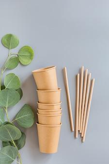 Vasos de papel y pajitas de papel ecológico sobre fondo gris.