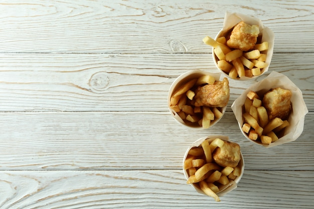 Vasos de papel con pescado frito y patatas fritas en madera