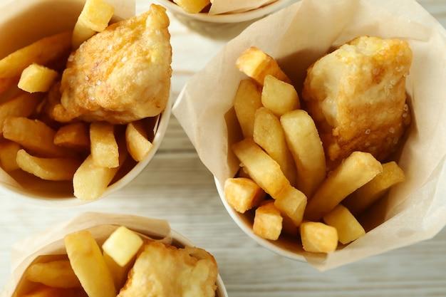 Vasos de papel con pescado frito y patatas fritas sobre fondo de madera