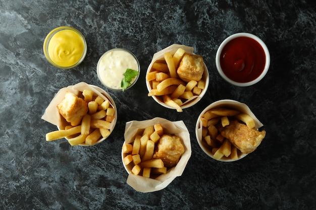 Vasos de papel con pescado frito y patatas fritas sobre fondo negro ahumado