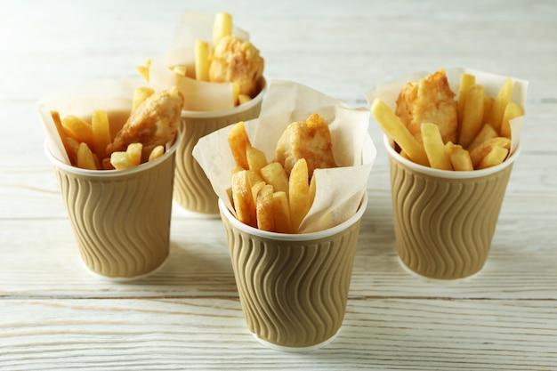 Vasos de papel con pescado frito y patatas fritas