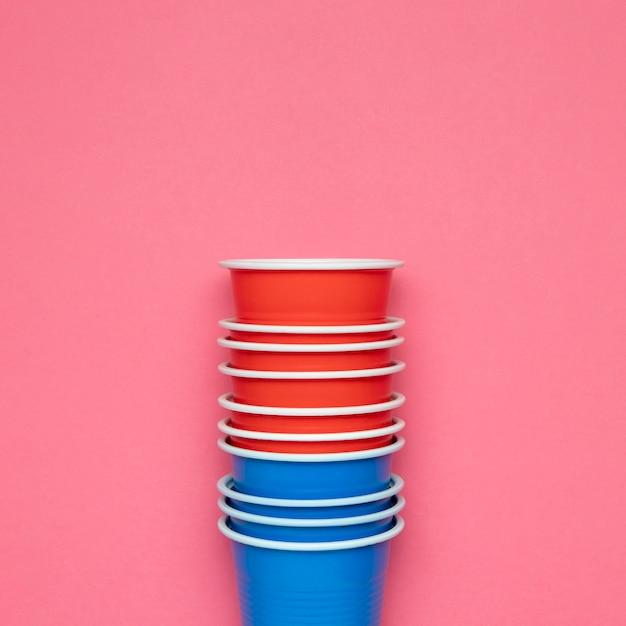 Vasos de papel sobre fondo rosa
