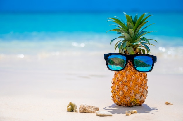 Los vasos de piña se encuentran en la playa junto al mar bajo el sol abrasador, estableciendo el concepto para el verano.