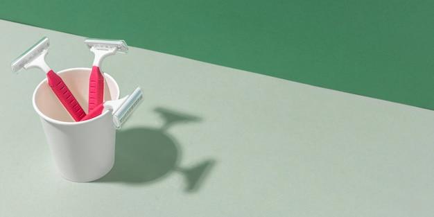 Vasos de plástico de alta vista y hojas de afeitar copie el espacio
