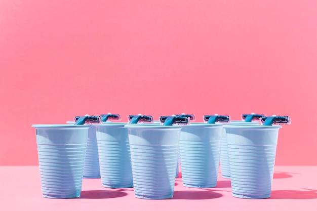 Vasos de plástico azul vista frontal y hojas de afeitar