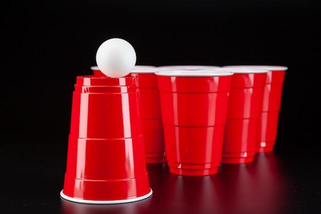 Vasos de plástico rojo y pelota para juego de cerveza pong