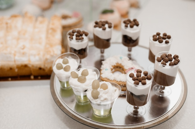 Vasos con una porción de postres de crema se colocan en la mesa de catering