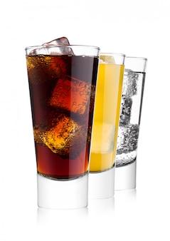 Vasos de refresco de cola y naranja y limonada agua con gas sobre fondo blanco con cubitos de hielo