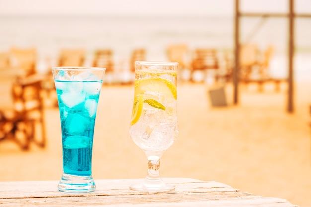 Vasos de refrescos de menta azul en mesa de madera