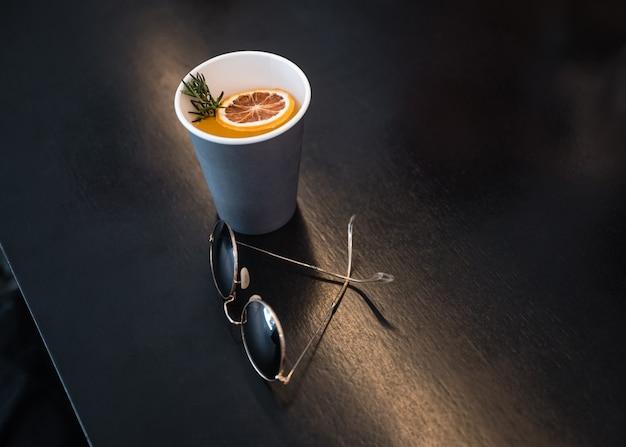 Vasos retro con café naranja en vaso de papel sobre mesa de madera