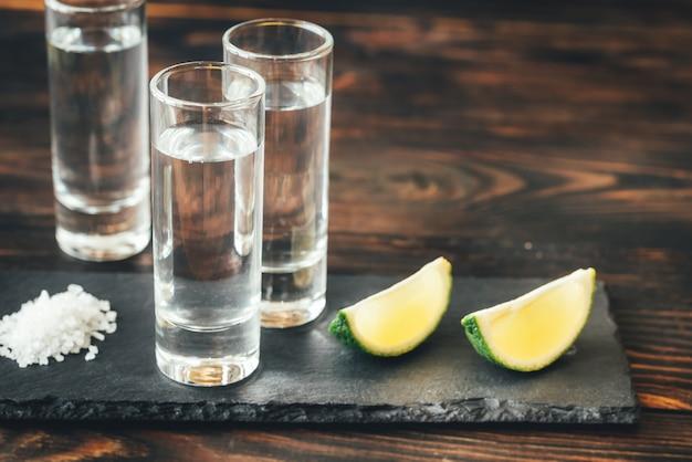 Vasos de tequila con rodajas de lima