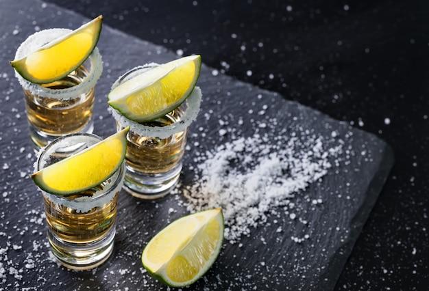 Vasos de tequila con sal en el borde y lima