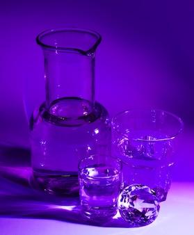 Vasos transparentes de agua; diamante y vaso sobre fondo púrpura