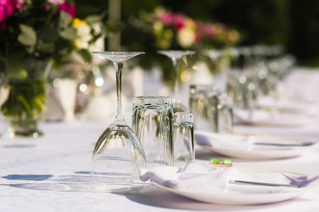 Vasos transparentes, servilletas y ramos de flores