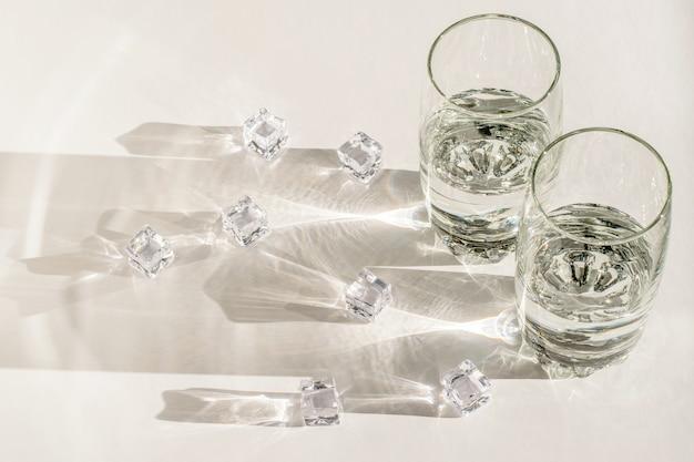Vasos transparentes, trozos de hielo y sombras largas y duras a la luz del sol