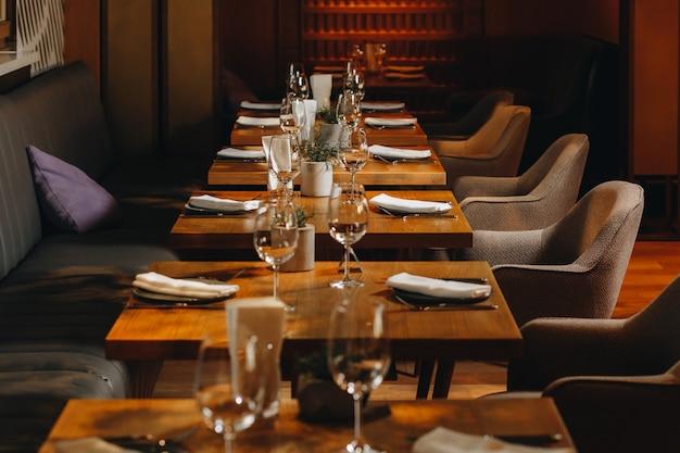 Vasos de vajilla, tenedor de flores, cuchillo servido para cenar en un restaurante con un interior acogedor