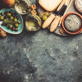 Vasos de vino blanco espumoso con queso, uvas, nueces, aceitunas y miel.