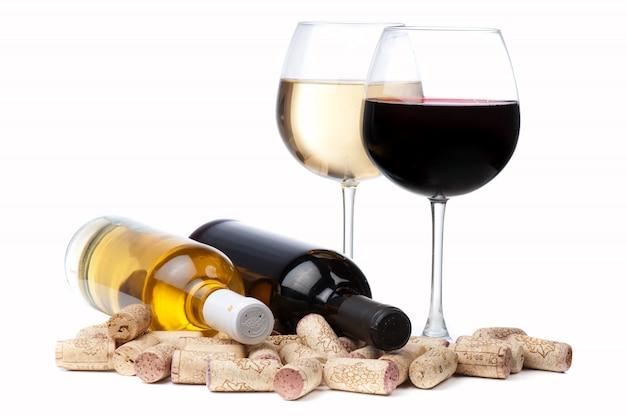 Vasos de vino blanco y tinto y corchos sobre blanco.