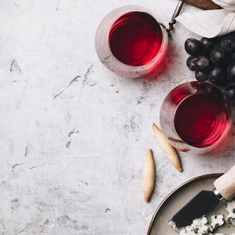 Vasos de vino tinto, queso y uvas en rústica mesa de hormigón
