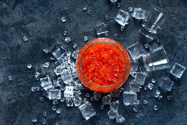 Vasos de vodka y caviar rojo en el hielo. bocadillo perfecto. vista superior.