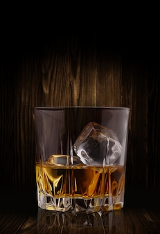 Vasos de whisky con cubitos de hielo sobre fondo de madera