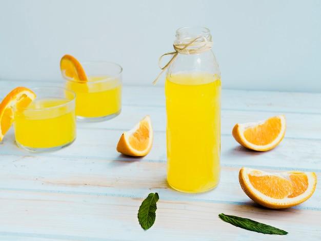 Vasos de zumo de naranja con fruta y menta.