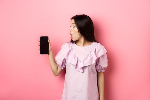 Vaya, mira aquí. chica asiática emocionada mira la pantalla del teléfono inteligente con cara de asombro, mirando la oferta en línea, de pie contra el fondo rosa.