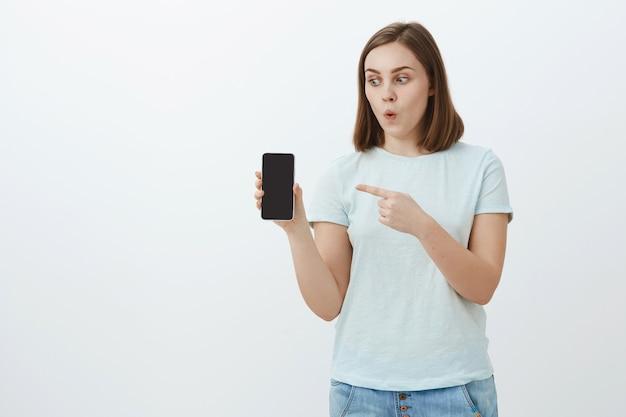 Vaya, mira lo que tengo. impresionada, entusiasta y guapa chica con cabello castaño corto doblando los labios con asombro apuntando a la pantalla del dispositivo mientras sostiene y mira un teléfono inteligente fresco sobre una pared blanca