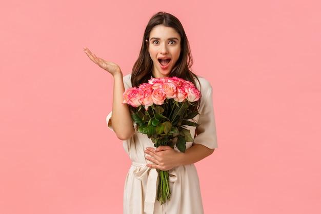 Vaya sorpresa tan maravillosa e inesperada. encantadora encantadora y romántica linda chica morena con vestido sobre pared rosa, recibe hermosas flores, sostiene rosas y se ve divertida, levanta la mano asombrada