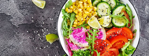 Vegan buda bowl. tazón con vegetales crudos frescos: pepino, tomate, rábano de sandía, lechuga, rúcula y maíz. ensalada fresca. comida vegetariana. vista superior. lay flat