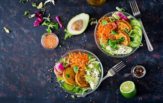 Vegano buda tazón cena mesa de comida. comida sana. tazón de almuerzo vegano saludable. buñuelo con lentejas y rábano, aguacate, ensalada de zanahoria. endecha plana.