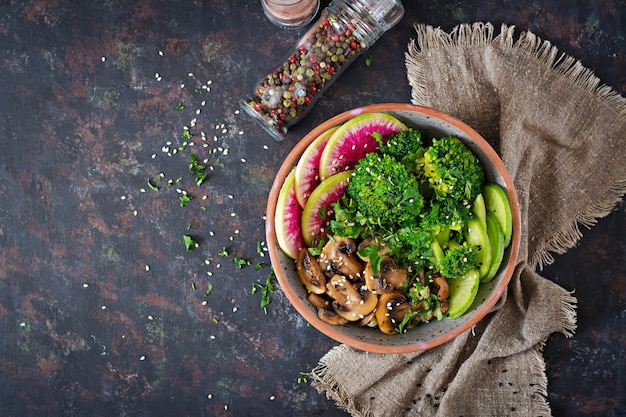 Vegano buda tazón cena mesa de comida. comida sana. tazón de almuerzo vegano saludable. champiñones a la plancha, brócoli, ensalada de rábano. endecha plana. vista superior.