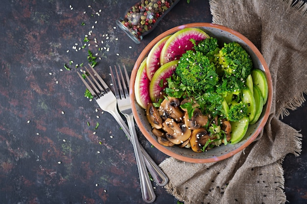 Vegano buda tazón cena mesa de comida. comida sana. tazón de almuerzo vegano saludable. champiñones a la plancha, brócoli, ensalada de rábano. endecha plana. .