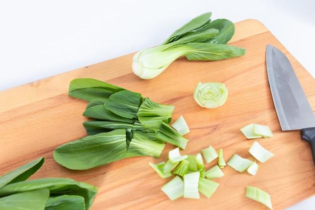 Vegetales cantoneses picados y condimentados colocados en una tabla para cortar madera desde la vista superior