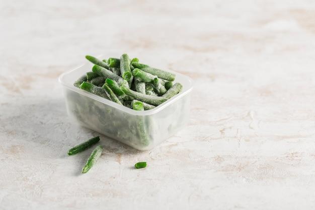 Vegetales congelados. judías verdes en un recipiente de plástico para congelar sobre un fondo claro.